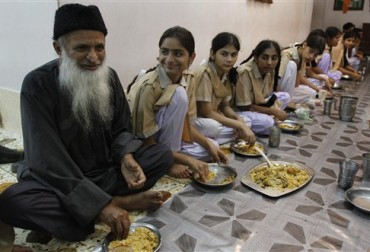 In this photo taken on July 24, 2010, humanitarian leader Abdul Sattar Edhi, left, has a meal with children living in one of his charity houses in Karachi, Pakistan. Edhi is a devout Muslim, but critical of Islamic clerics in general, not just extremists. He says they focus on ritual, preaching hellfire and defending the faith against imagined enemies, rather than helping the poor _ which he says should be the cornerstone of all faiths. (AP Photo/Shakil Adil)